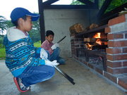 夕食づくり、火おこしは任せてと少年たち
